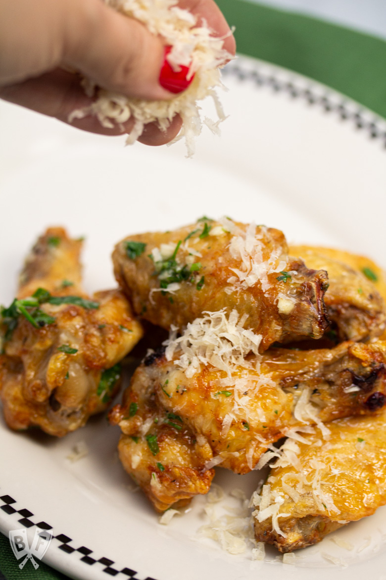 Sprinkling Parmesan cheese on air-fried chicken wings