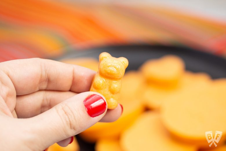 Hand holding a bear shaped Tangerine Coconut Jelly