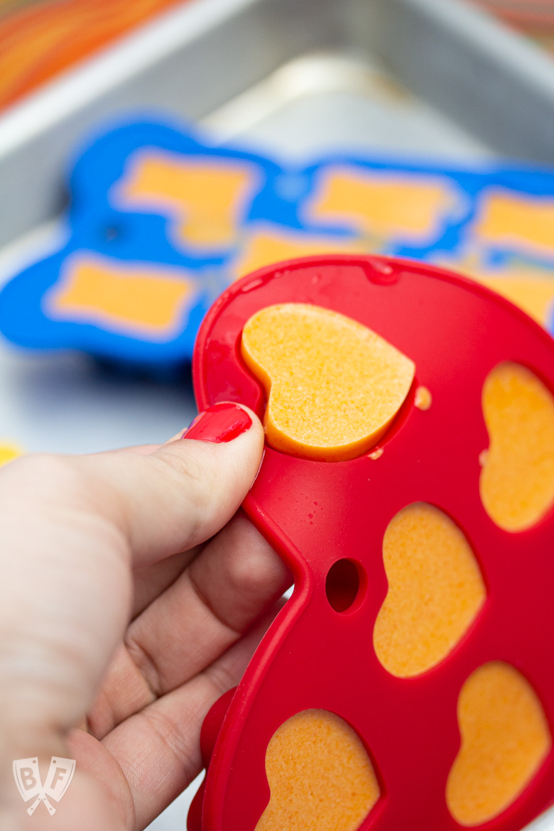 Hand popping a Tangerine Coconut Jelly out of a heart shaped mold