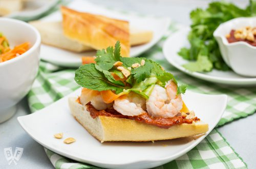 Vietnamese shrimp sandwich on a plate piled with pickled veggies, fresh herbs and peanut sauce.