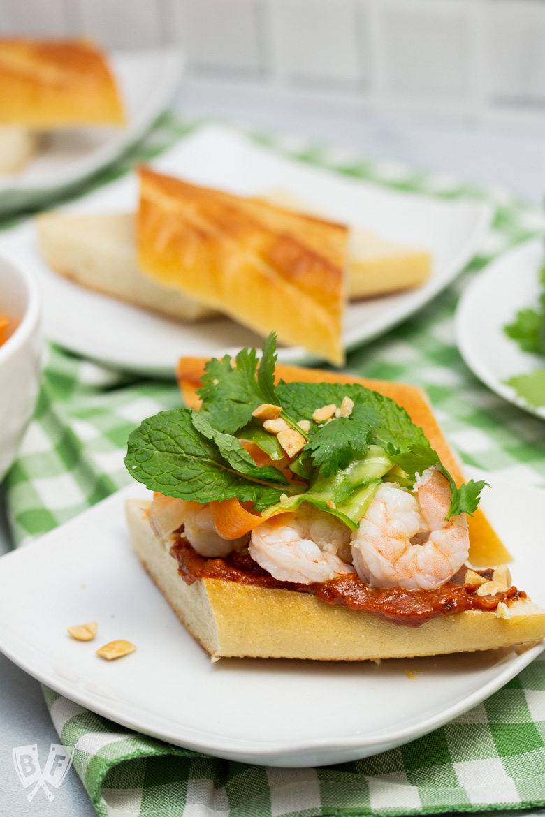 One Vietnamese shrimp sandwich assembled with ingredients alongside for more