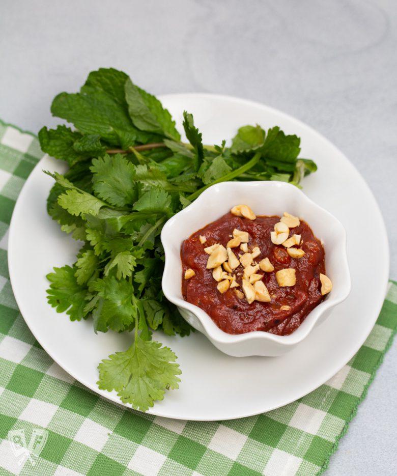 Bowl of Vietnamese peanut sauce with fresh herbs alongside