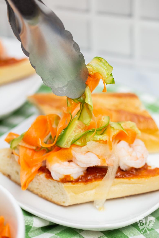 Adding pickled vegetables to a Vietnamese shrimp sandwich