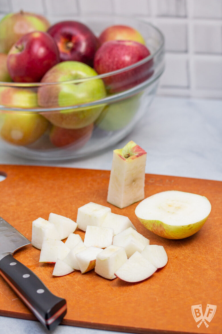 Apples being cut on a cutting board with a bowl of apples in the background.