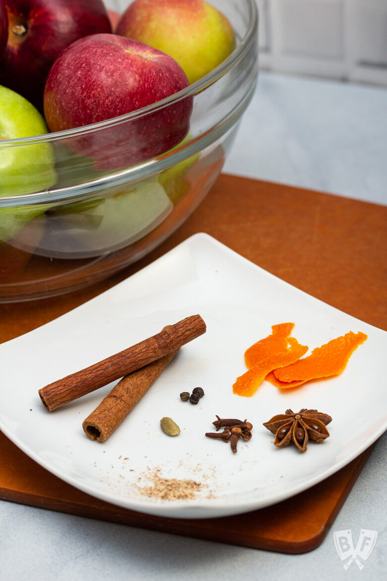 Mulling spices on a plate in front of a bowl of apples.