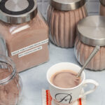 An assortment of jars of hot cocoa mix with a mug of hot chocolate up front.