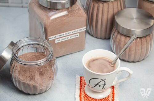 Homemade hot cocoa in a mug surrounded by jars of hot cocoa mix.