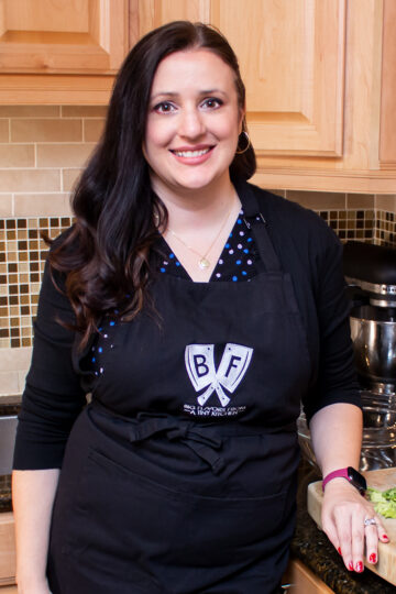 Ashley Covelli standing in the kitchen next to a cutting board full of ingredients, wearing an apron with the Big Flavors logo.
