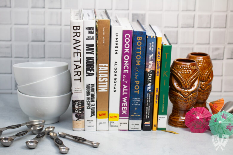 Assortment of cookbooks with measuring spoons, bowls, and tiki cocktail supplies alongside.