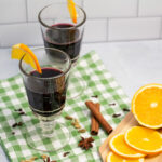 Two glasses of mulled wine surrounded by spices and orange slices.