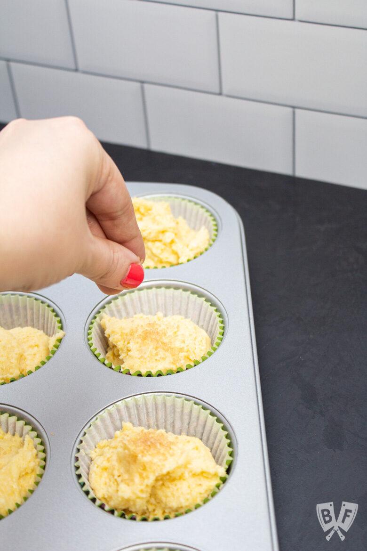 Sprinkling turbinado sugar on top of sweet corn muffins.