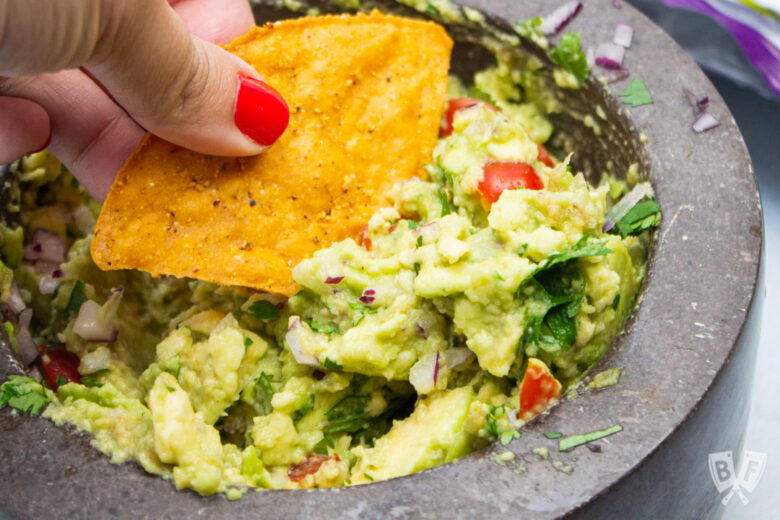 Tortilla chip scooping up guacamole.