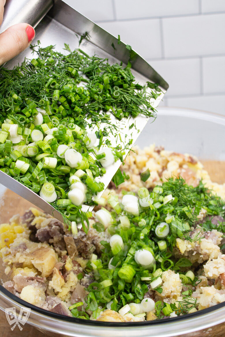 Adding fresh herbs and green onions to a bowl of smashed potatoes for herbed potato salad.