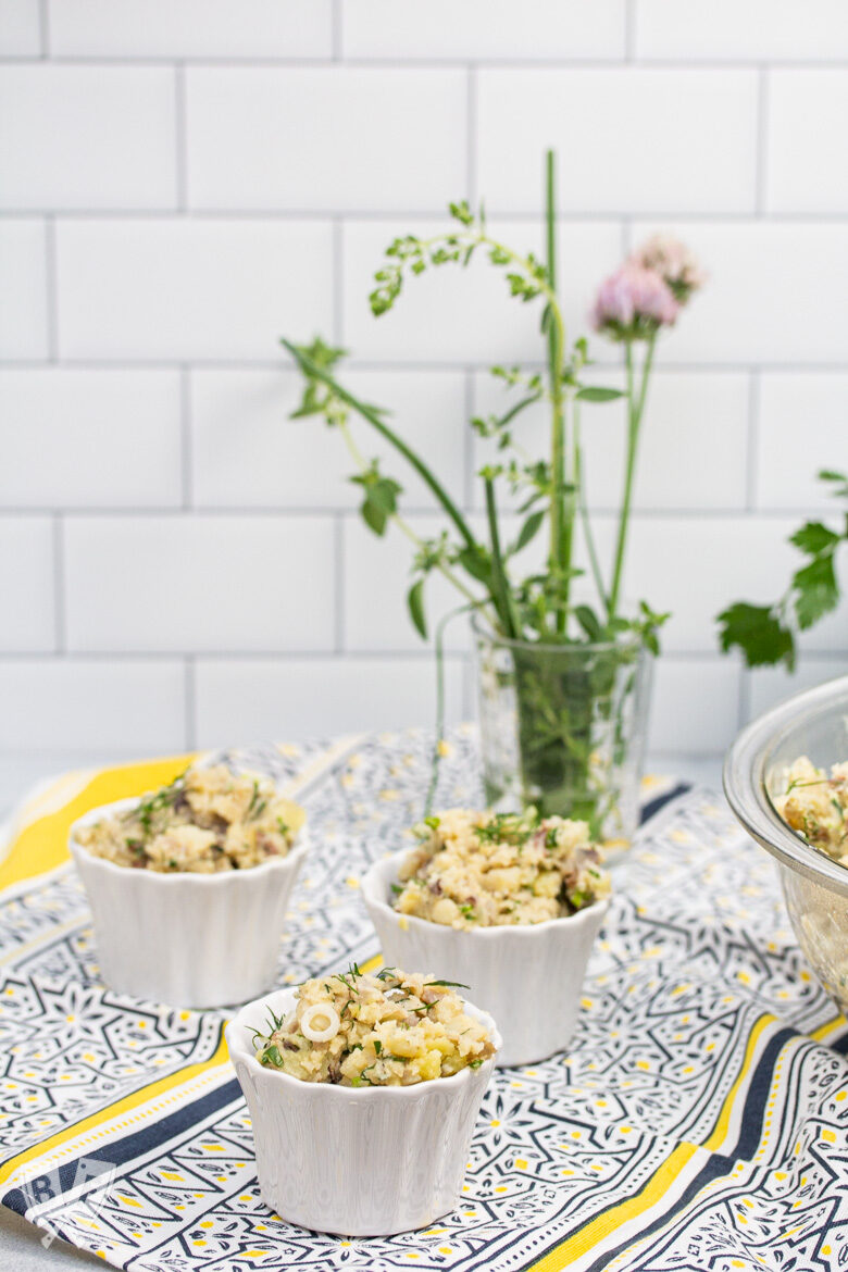 Ramekins of potato salad with fresh herbs in the background.