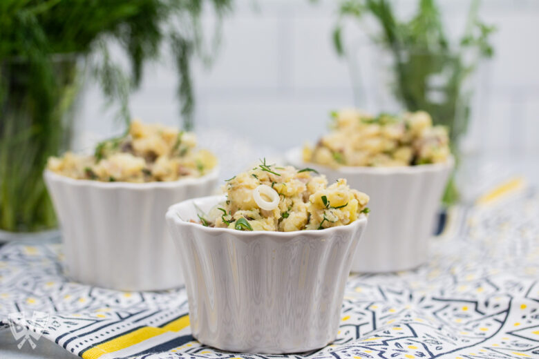 3 containers of potato salad with fresh herbs in the background.