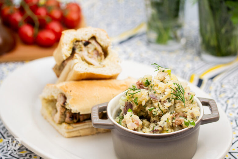 Herbed potato salad on a plate with a grilled chicken sandwich.