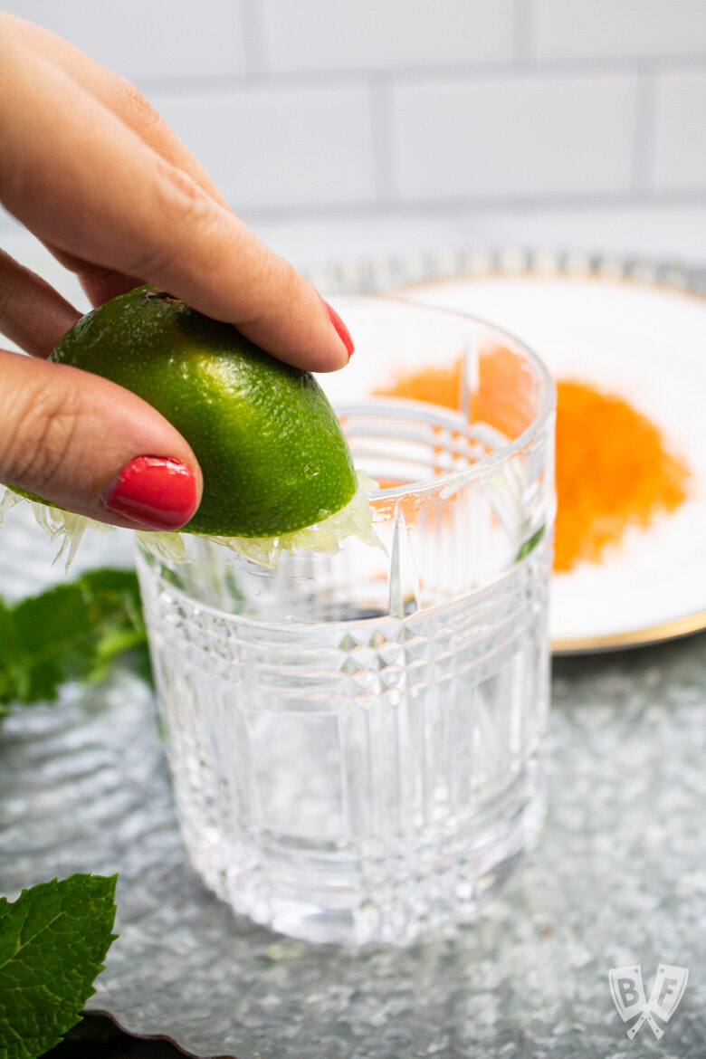 Rubbing a lime on the rim of a cocktail glass.
