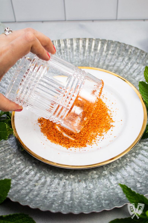 Rimming a cocktail glass with Tajín seasoning.