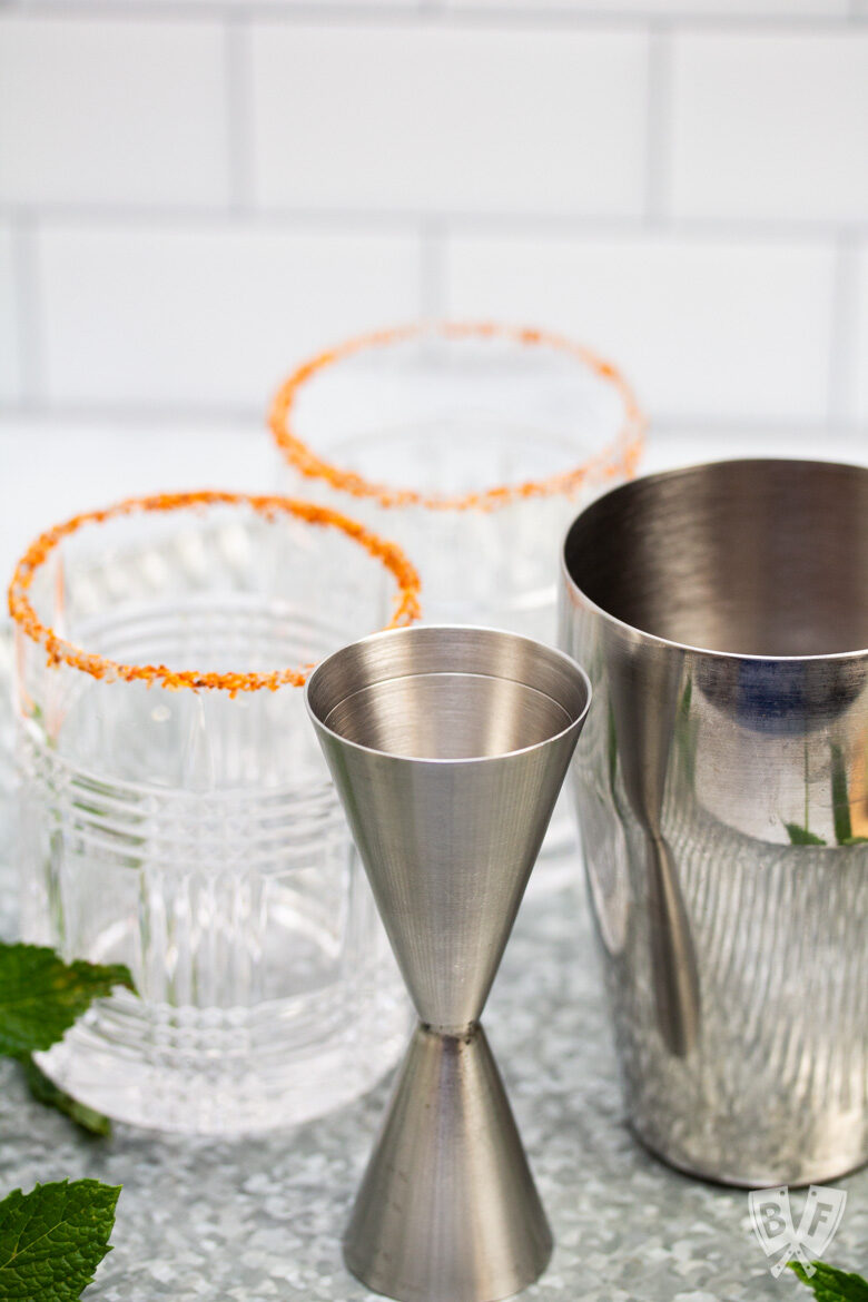 Tajín rimmed cocktail glasses with a jigger and cocktail shaker.