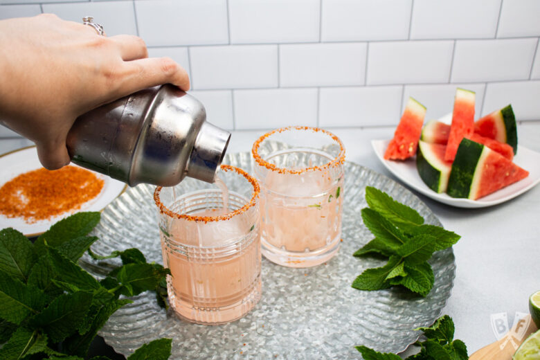 Pouring a watermelon and tequila cocktail into Tajín rimmed cocktail glasses.