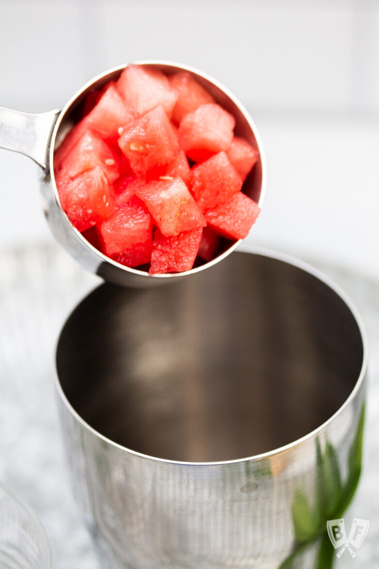 Pouring cubes of watermelon into a cocktail shaker.