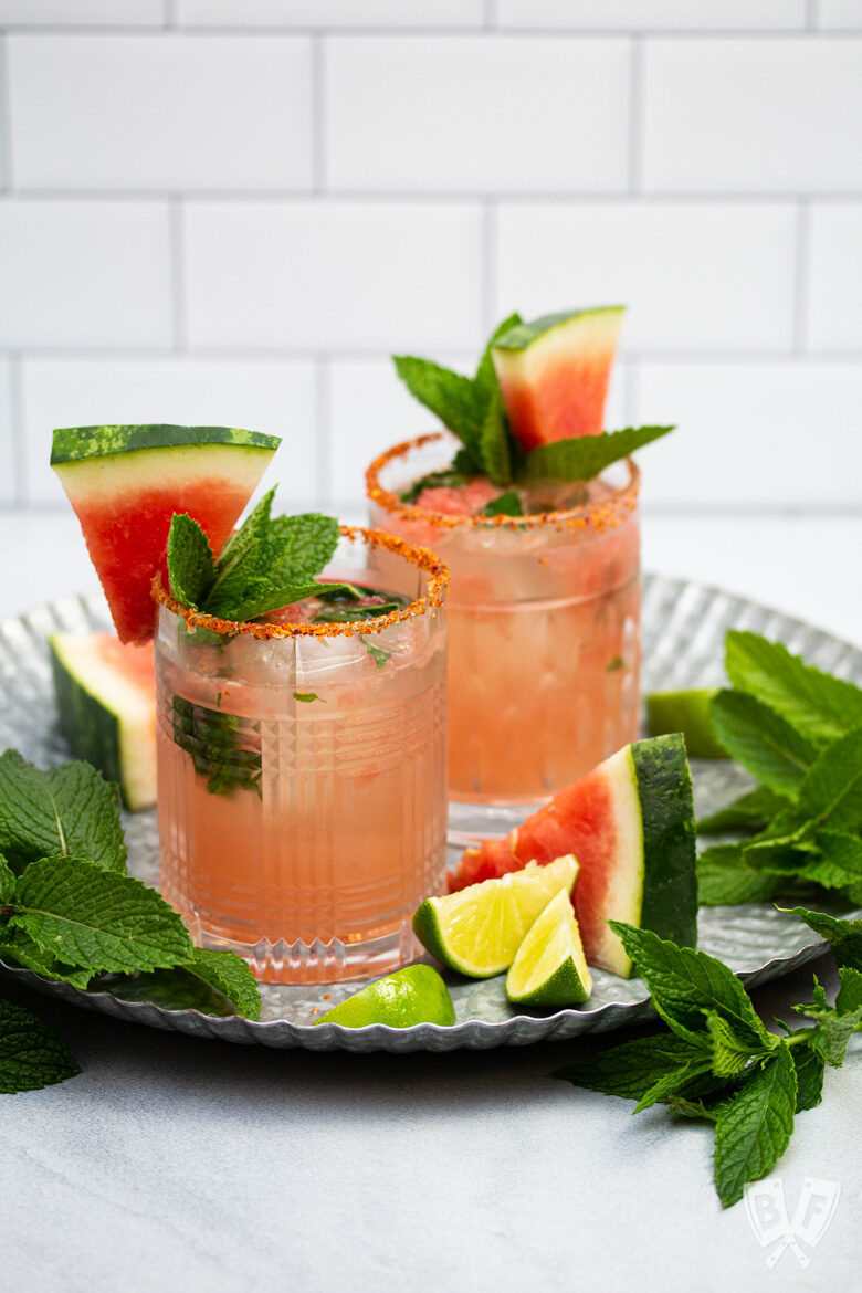 Watermelon cocktails on a tray garnished with fresh mint, watermelon, and lime.