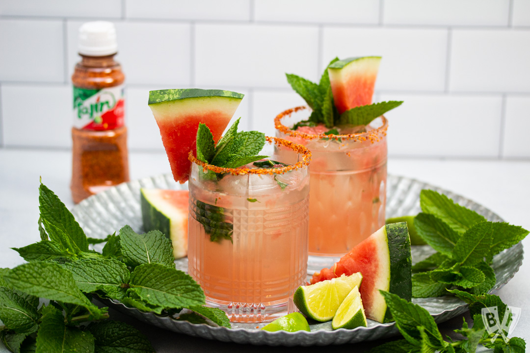 Tray of cocktails made with watermelon, mint, lime, and tequila with a bottle of Tajin seasoning in the background.
