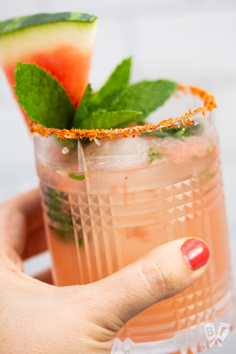 Hand holding a glass with a watermelon cocktail garnished with fresh mint and watermelon with a Tajin rim.