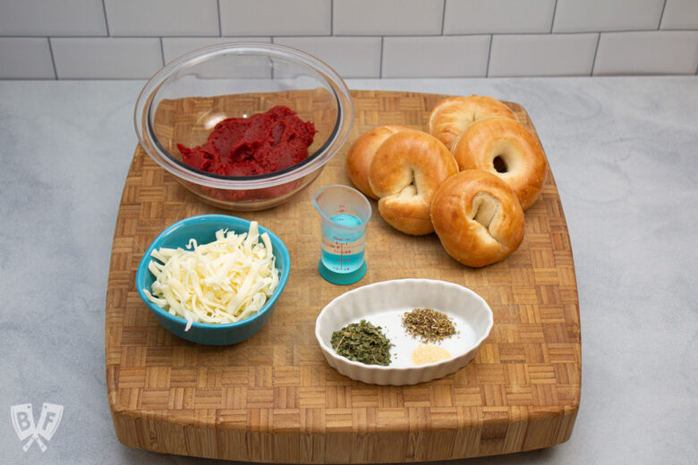 Ingredients for homemade mini pizza bagels on a butcher block.