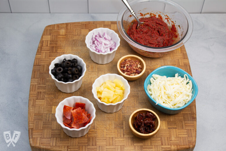 Board topped with bowls full of pizza sauce and toppings.
