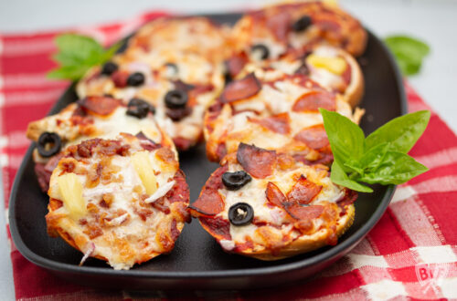 Close up of assorted mini pizza bagels on a platter.