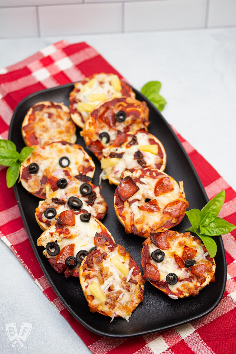 Platter of 10 assorted mini pizza bagels with fresh basil.