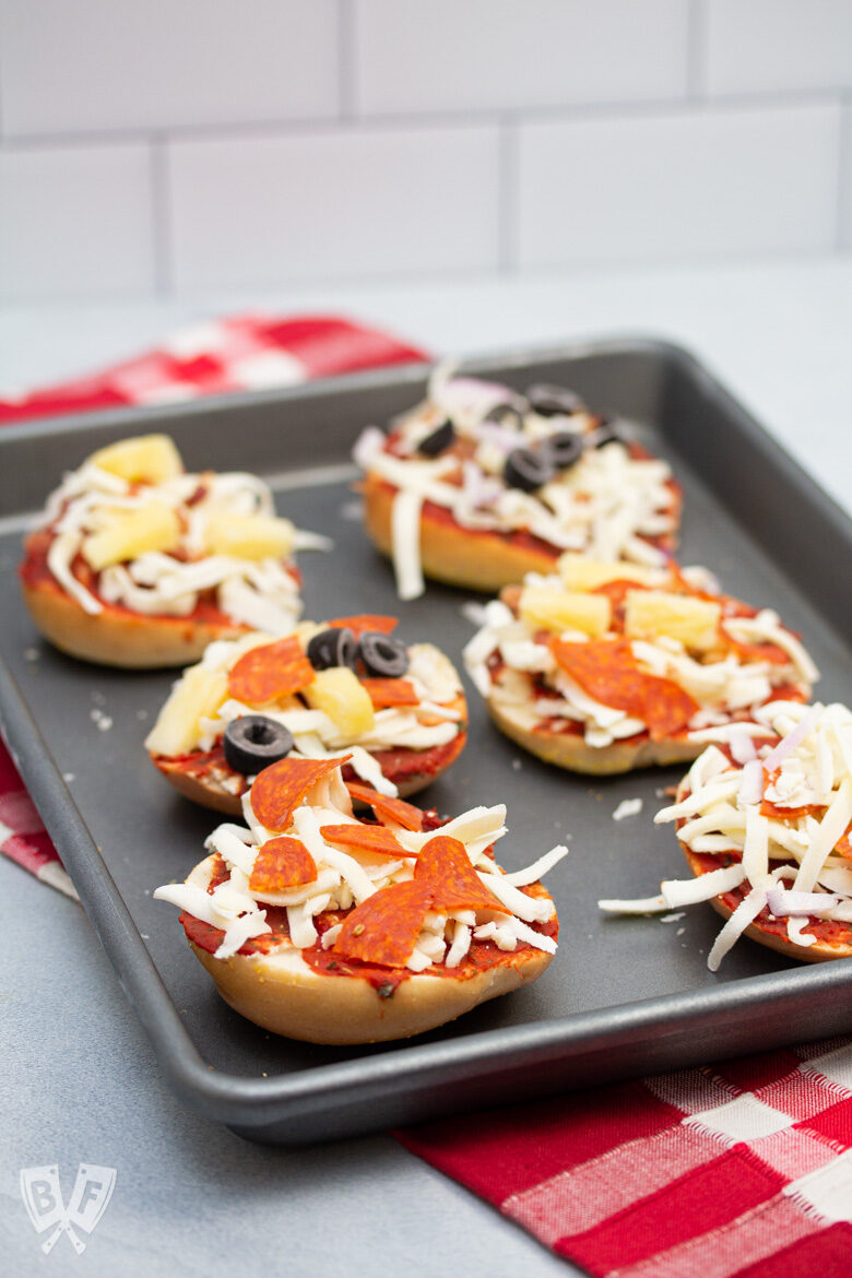 6 assorted mini pizza bagels on a sheet pan.