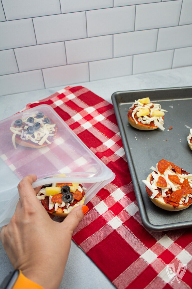 Tray of mini pizza bagels on the side with a hand placing some in a freezer bag.