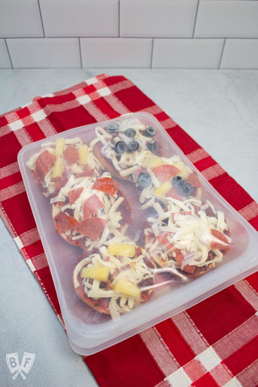 Reusable freezer with mini pizza bagels inside.