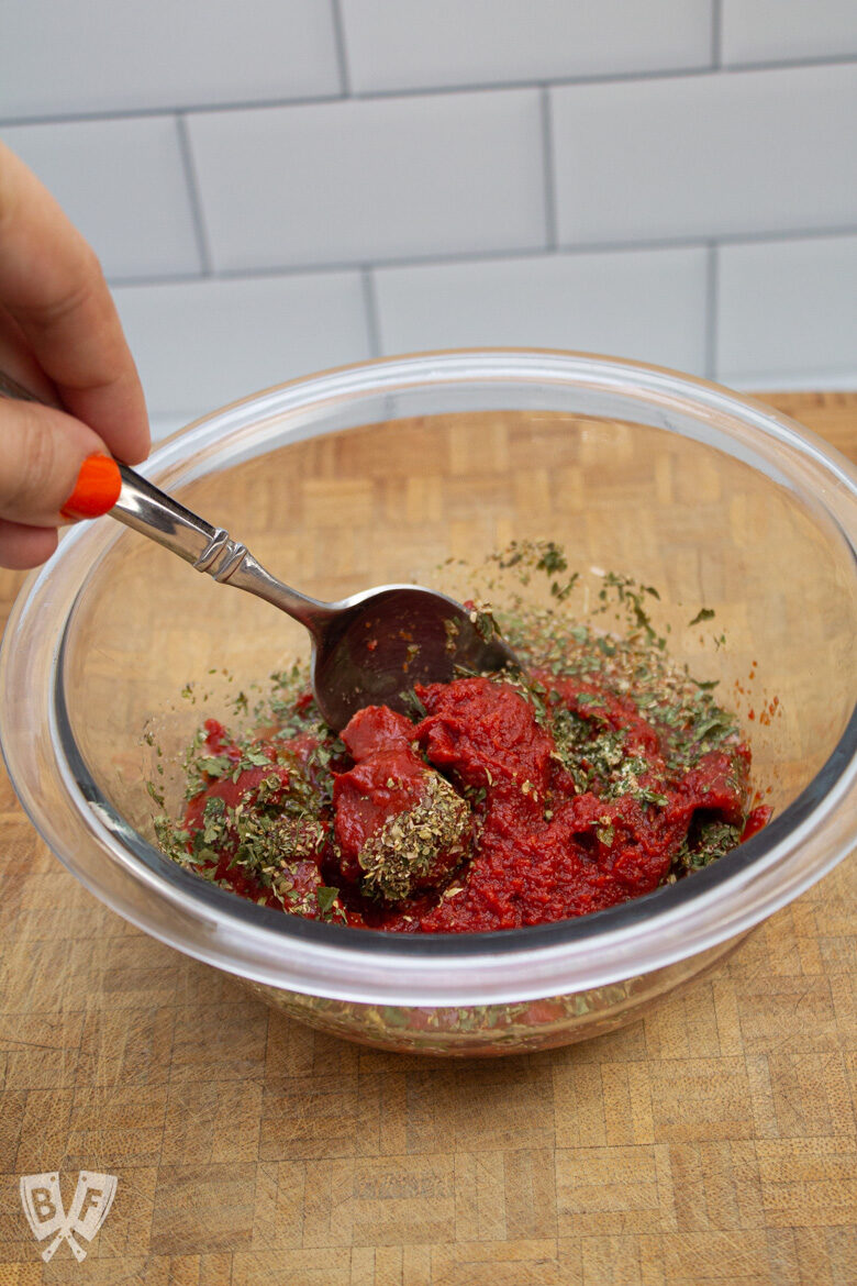 Mixing homemade pizza sauce ingredients in a bowl.