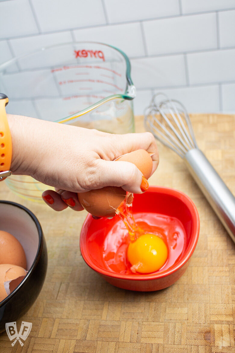 Hand cracking an egg into a small bowl.