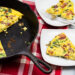 Frittata in a cast iron skillet with a few slices taken out on plates to the side.