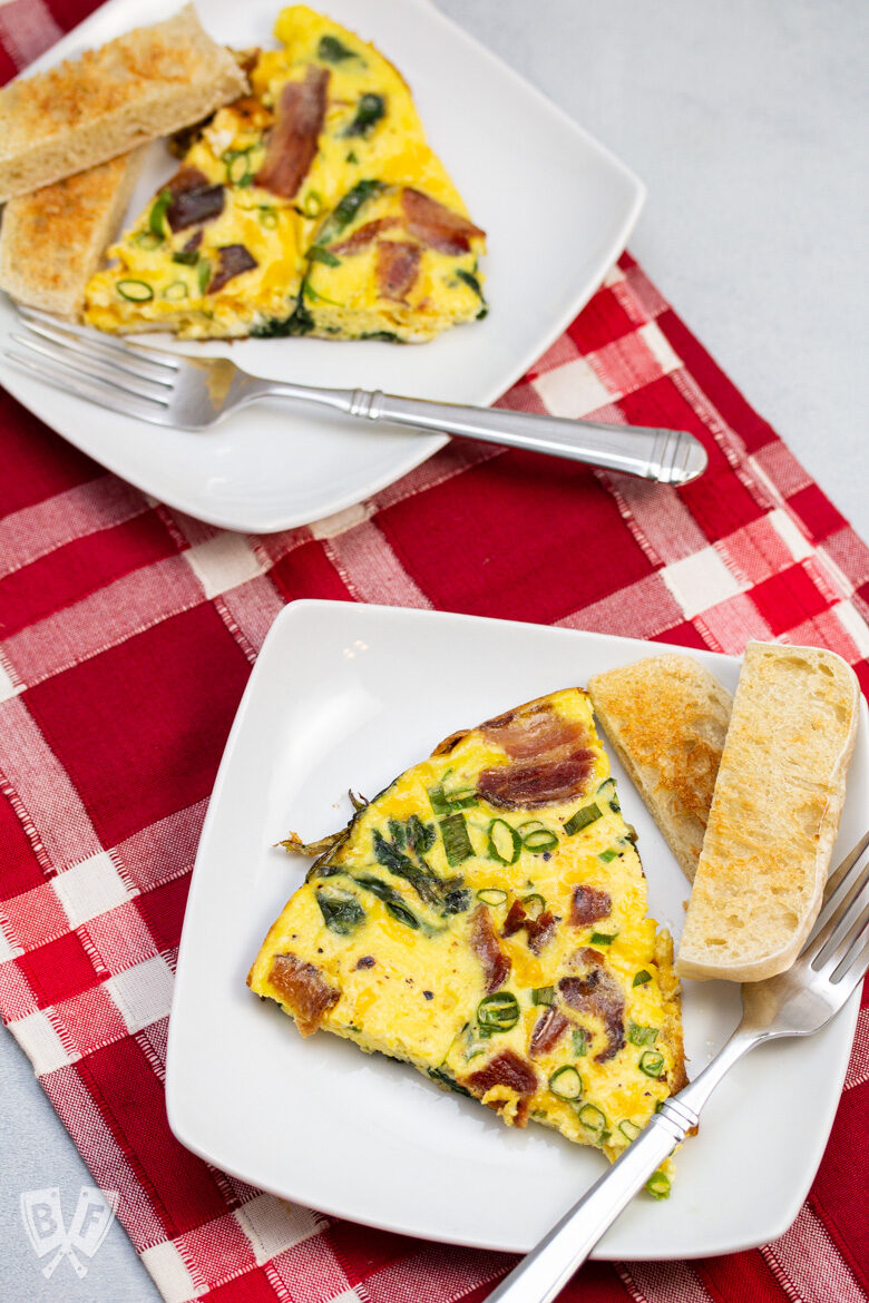 Two wedges of spinach, bacon, green onion, and cheddar frittata with toasted English muffin slices.