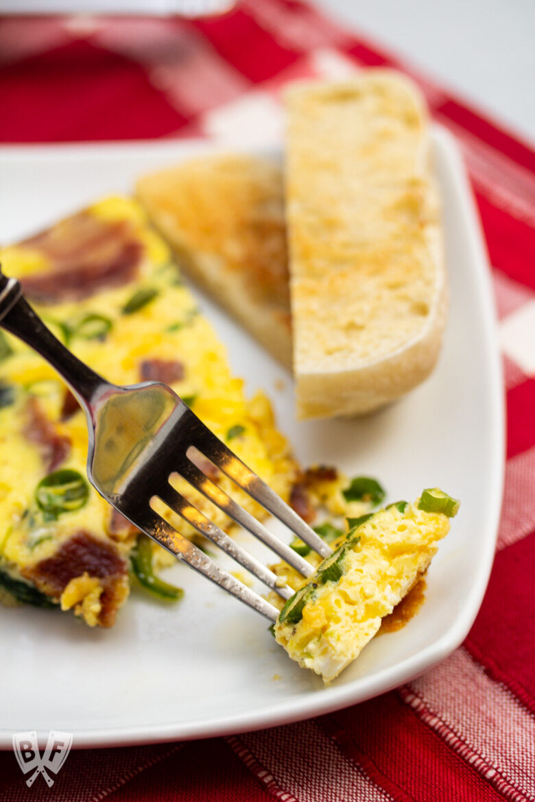 Close-up of a fork taking a piece from a spinach, bacon, green onion, and cheddar frittata.